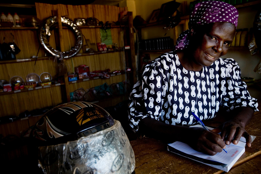 Dolphine Aluocho Ele, 49 years old and a widow, writes a receipt in her shop that sells spare parts for motor bikes near Bondo, Kenya. Dolphine is Chairperson of the Nango Women's Association that is part of the GL and S programme. (Photo: Kate Holt/CARE)