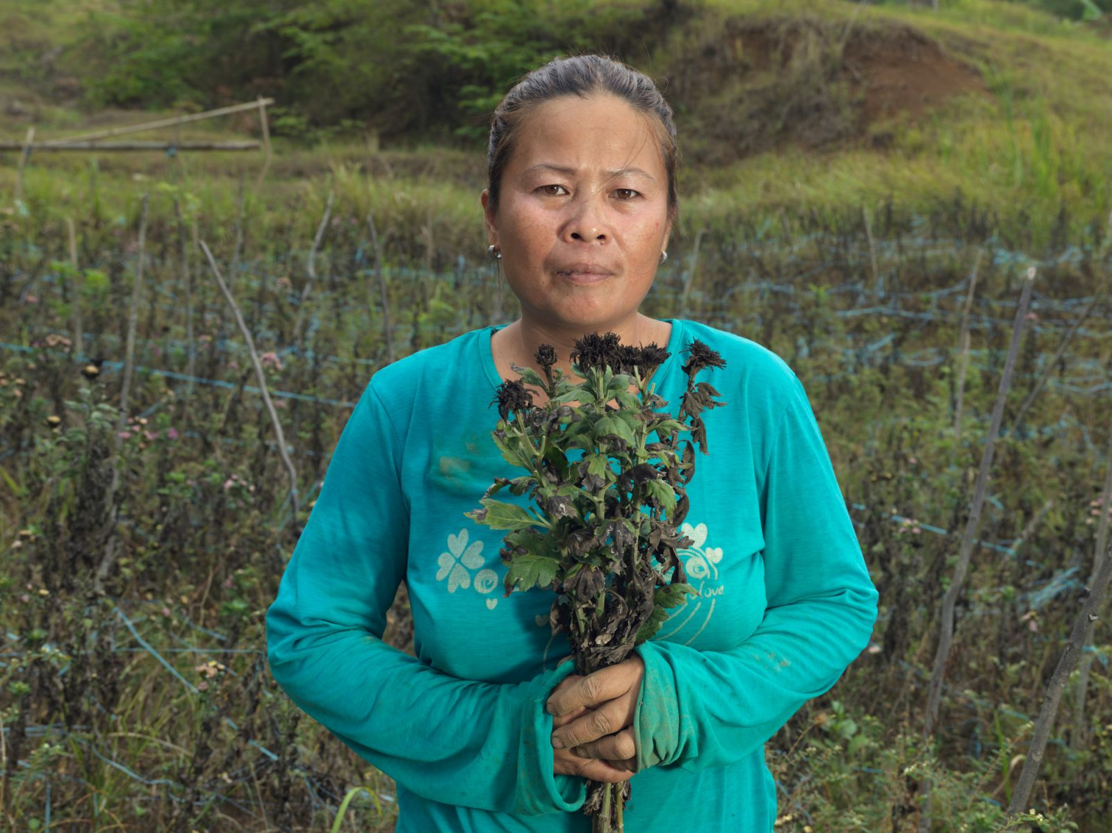 Wilma Delima holds dead flowers due to a failed harvest in Philippines. She wants to use the money for selling flowers to invest in her children's education. (Photo: Peter Caton/CARE)