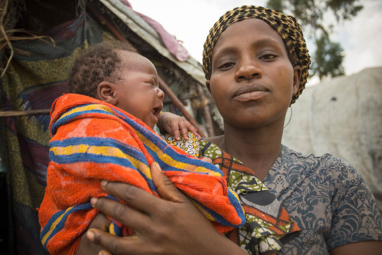 Josephine Marciane (37), shown here with her infant daughter Naomi Gladis, is a survivor of sexual and gender based violence. After being raped while pregnant with her and her husband's baby, her husband left the family. Today she lives with her 9 children in Lac Vert Camp near Goma, DRC, where she receives support from CARE in the form of cash distribution, psycho-social support,