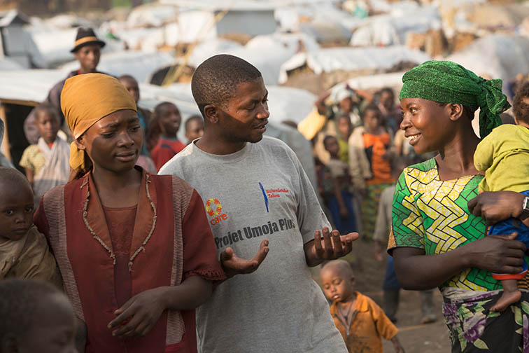CARE DRC Food Security Manager, Joseph Kakuru, talks with IDP's in Kishusha – Rubaya Camp in Masisi Territory, North Kivu Province in Eastern DRC including Muneza Francine (right) and Furaha Tuisenge (left). CARE is working in the camp to help survivors of Sexual and Gender-Based Violence and to provide emergency assistance to people displaced by the conflict. CARE/Jake Lyell