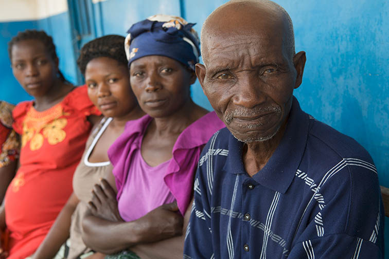 "Mr. Francois Xavien (68), shown here with members of the Umoja Ni Nguvu (""Unity is Power"") Income Generation Group, is an advocate for women's rights in his community in Goma, DRC. ""In the past men used to despise women. However, with this new generation and new way of thinking, men and women have become equal,"" says Mr. Xavien. CARE/Jake Lyell"